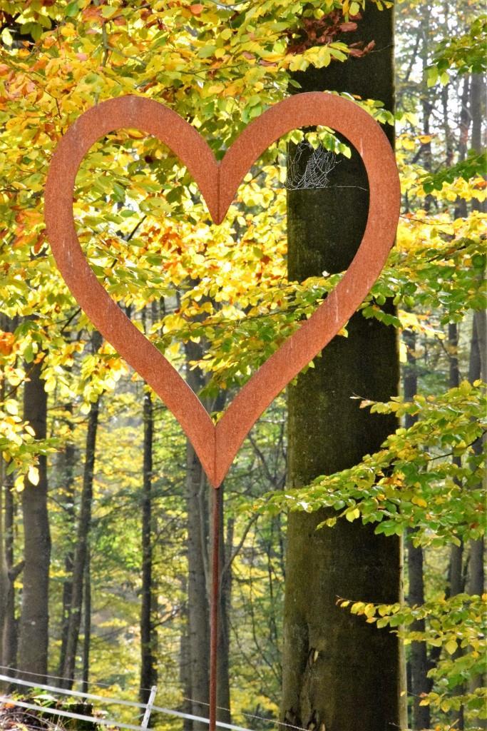 I LOVE FALL - rostiges Herz auf Eisenstab vor dem Herbstwald