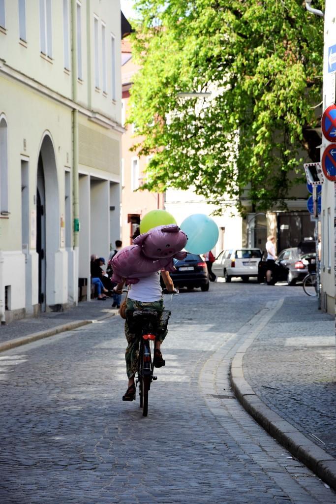 Schwein gehabt! Radlerin unterwegs mit Ballons in der Regensburger Altstadt
