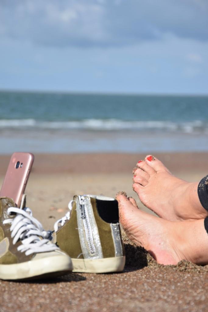 Einfach mal Pause machen am Strand. Schuhe aus, Füße in den Sand, Handy auf Offline